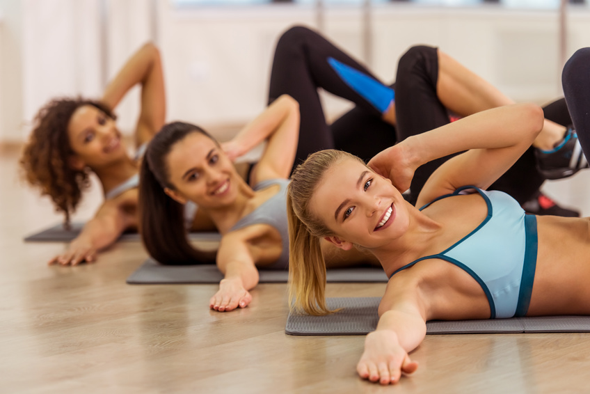 Three attractive sport girls smiling while working out lying on yoga mat in fitness class. Beautiful blonde girl looking at camera